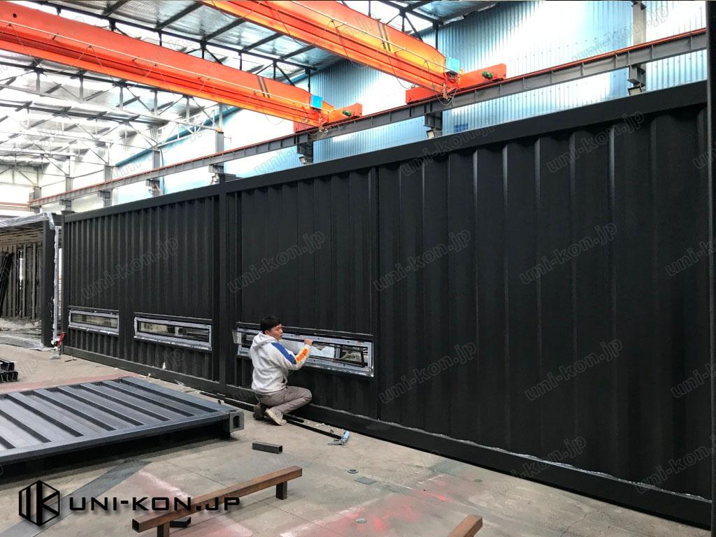 コンテナハウス工場内で、中国製アルミ建具にペアガラスを装着しているところです